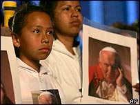 Worshippers hold pictures of the Pope at a Mass in Mexico City