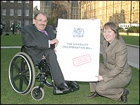 Photo of Bert Massie and Maria Eagle holding an enlarged copy of the bill