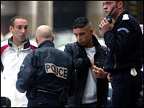 French police check the ID of passers-by on the Champs Elysees in Paris
