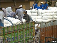 Pakistani labourers unload relief goods at the Wagah border post 