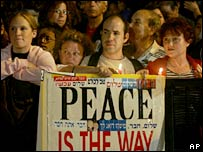 Israelis hold candles and a banner at a rally in Tel Aviv