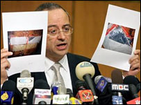 Jordanian Deputy Prime Minister Marwan Muasher show photographs of a suicide bomb belt