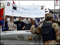 Iraqi soldiers stand guard as Iraqis holding up banners flock towards Firdus Square