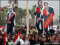 Protesters carrying effigies of Saddam Hussein, Tony Blair and George W Bush