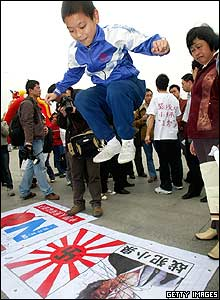 A Chinese boy jumps on an anti-Japanese poster