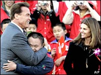 Arnold Schwarzenegger embraces Special Olympics athlete Wang Xiaoyu, as his First lady Maria Shriver looks on