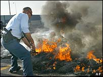 A police officer tries to put out burning tyres near Tel Aviv