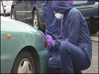 A scenes of crime officer examines the car