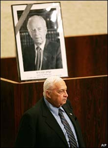 Israeli Prime Minister Ariel Sharon pauses by a portrait of Yitzhak Rabin in the country's parliament, the Knesset.