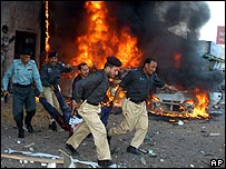 Police remove a body from the scene of the Karachi bombing