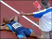 Jon Drummond of the USA lies on the track in protest after being disqualified for a false start during the quarter final of the men's 100m at the World Championships in 2003.