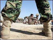 An Iraqi soldier guards Iraqi prisoners in Baghdad (file photo)