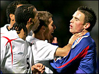 Gary O'Neil and Anton Ferdinand square up to France's Anthony Le Tallec