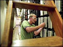 A BT engineer working inside a telephone exchange