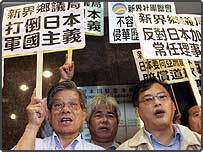 """Protesters raise placards that read """"Overthrow Japan's militarism"""" during a protest outside Japan's consulate in Hong Kong"""