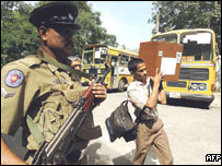 Police on guard as election worker carries ballot boxes in Colombo