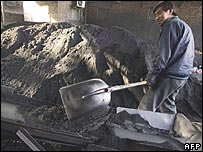 Chinese worker shovelling coal