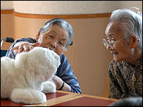 Two elderly women play with Paro