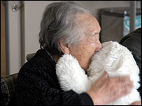 Japanese woman cuddles Paro