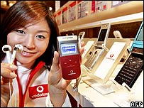 A Japanese woman holding up a Vodafone phone