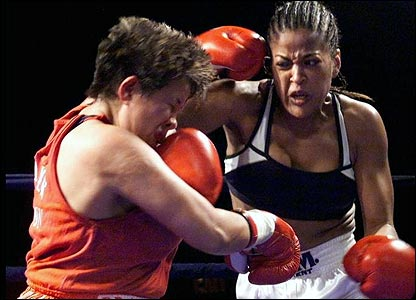 Laila Ali (right) punches Crystal Brave Heart Arcand