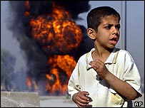 A Iraqi boy stands near a burning tanker truck after insurgents hit an American fuel-supply convoy in Baghdad