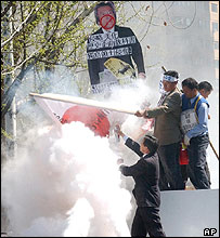 Officials extinguish a fire set by protesters to burn a Japanese flag during a rally in Seoul, 13/4/05