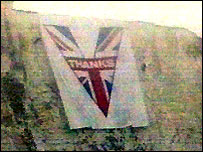 The Victory flag draped over Dover's white cliffs