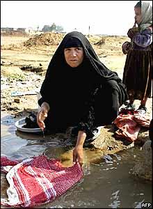 Iraqi woman washing clothes in stream