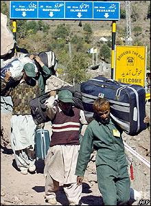 Porters carry goods across the Kashmiri Line of Control