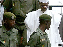 Hissene Habre being escorted from a Senegalese court by guards.