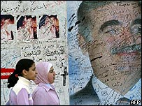 Lebanese schoolgirls walk past a mural of Rafik Hariri