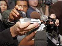 Reporters listen to Robert M�nard on a mobile phone