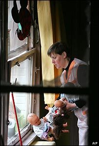 Woman carries dolls out of the Broca nursery school in Fives, Lille