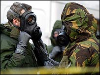 Soldiers wearing gas masks prepare to enter the house in Manchester where Det Con Stephen Oake was killed