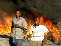 People run from a fire lit in Mombasa, Kenya, where a 'No' campaign rally was dispersed by police.