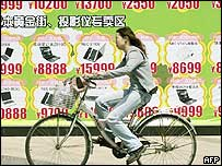 Woman cycles past a billboard showing computers in China