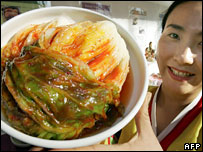 Korean woman holding up dish of kimchi