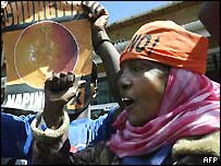 "Supporters of the Kenyan constitution ""No"" campaign hold up a poster of an orange"