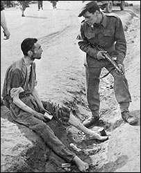 British solider talking to inmate at Belsen camp, 1945