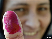 An Egyptian women holds up her thumb showing she has voted in parliamentary elections