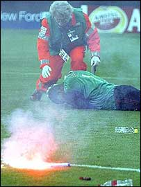 Nelson Dida lies prostrate after being felled by a flare