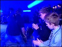 Peter Hook plays as schoolchildren watch on