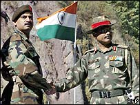 Pakistan and India army officers shake hands as they open a border crossing