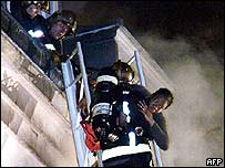 Firefighters rescue a guest from a fire in a hotel in Paris