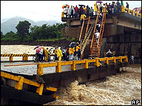 Residents try to cross a collapsed bridge in Monga, north Honduras