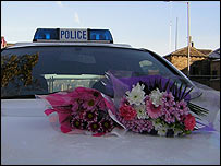 Bouquets on police car bonnet