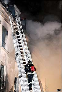 A firefighter climbs towards an upper window of the burning hotel