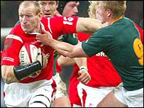 Wales captain Gareth Thomas hands off South Africa scrum-half Michael Claassens