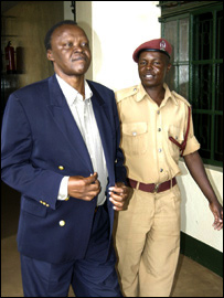 Cecafa boss Dennis Obua is escorted from jail by a policeman